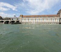 Ein altes Wasserkraftwerk am Rhein und bviel Wasserim Vordergrund.