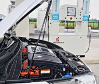 Blick auf die geöffnete Motorhaube eines Brennstoffzellen-PkWs vor einer Wasserstoff-Zapfsäule.