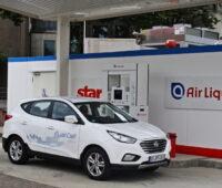 Ein Wasserstoffauto steht vor einer Tankstelle.