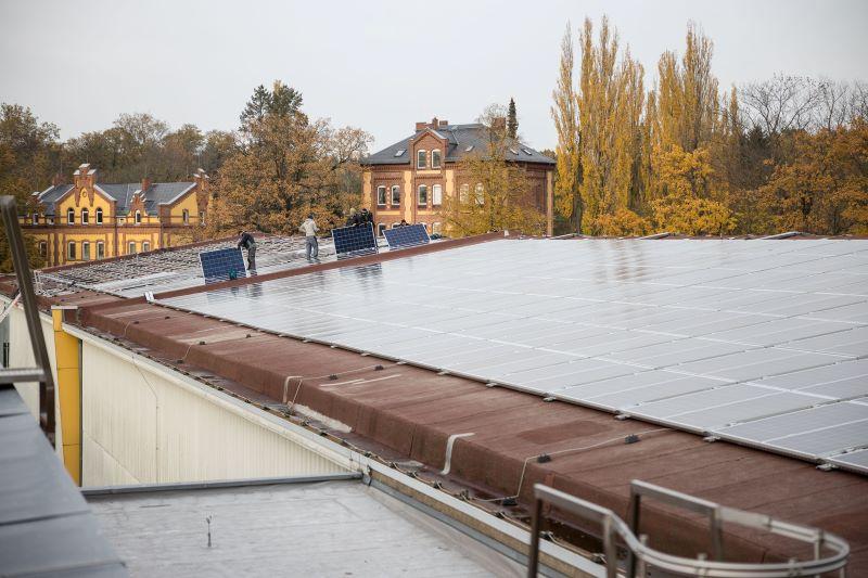 Montage von Solarmodulen auf einem hitorischen Wasserwerk im Herbstlaub.