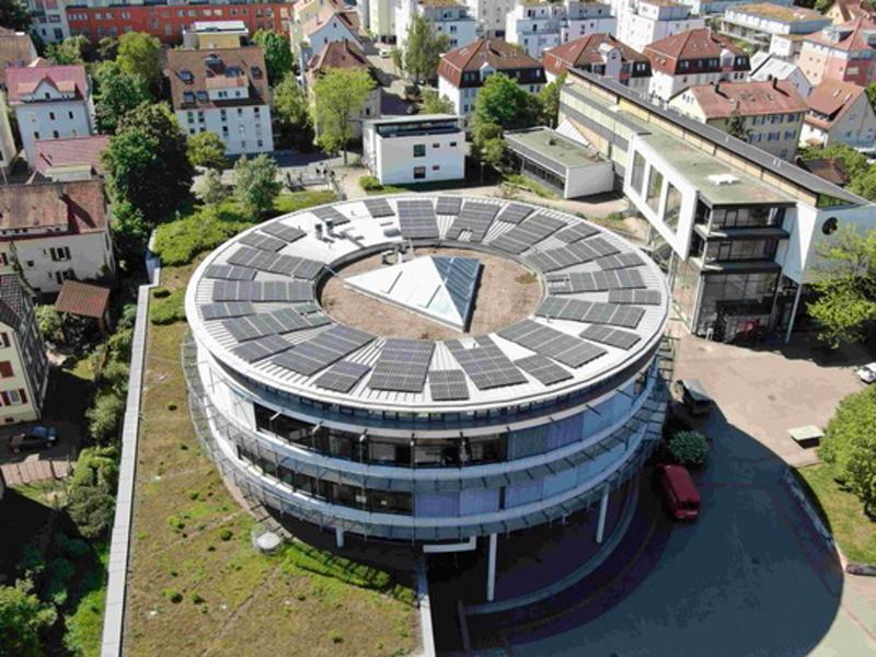 Luftbild eines runden Gebäudes mit Solarmodulen auf dem Dach.