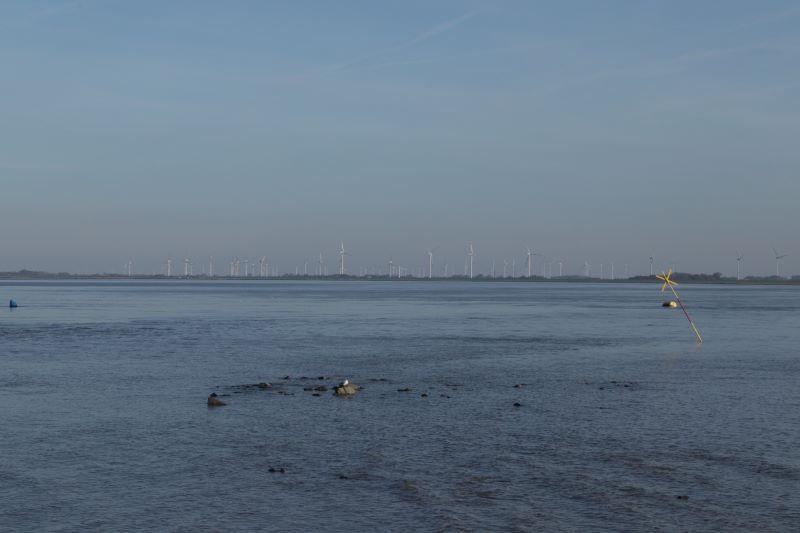 Im Vordergrund im Eidersperrwerk an der Nordsee. Im Hintergrund schememhaft Windkraftanlagen