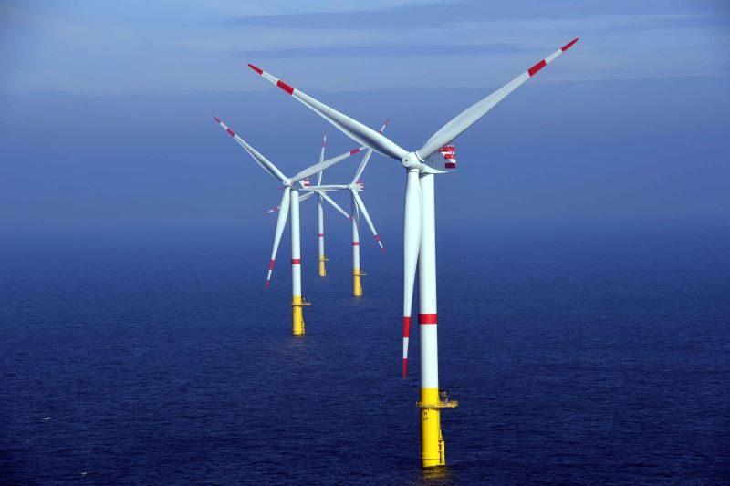 Mehrere Windkraftanlagen stehen im Meer. Rundherum blaues Wasser, das am Horizont in den ebenfalls blauen Himmel übergeht.