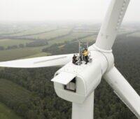 Menschen auf der Gondel einer Windenergie-Anlage.