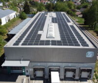Das Dach eines Industriegebäudes ist komplett mit Solarstrommodulen bestückt.