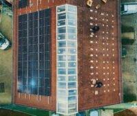 Vogelperspektive auf ein Spitzdach mit Solaranlage auf linker Seite.