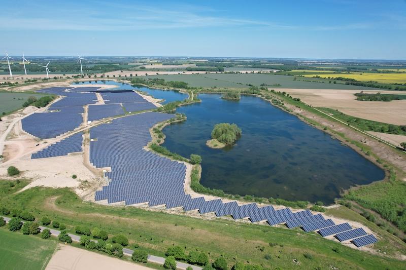 Luftbild einer PV-Freiflächenanlage neben einem See.