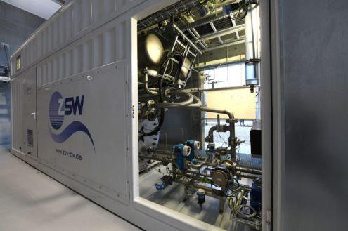 Foto eines großen Metallcontainers mit geöffneter Tür. Darinnen ist der eigentliche Elektrolyseur zu sehen.