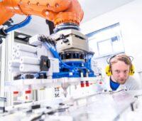 Ein Forscher beobachtet eine automatisierte Fertigung unter einem Roboterarm.