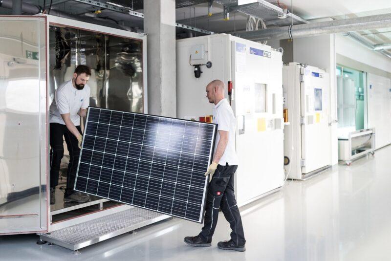 Zu sehen sind zwei Forscher mit einem Modul im Testzentrum für die potenzialinduzierte Degradation von Photovoltaik-Modulen beim ZSW.