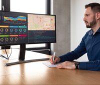 Zu sehen ist ein Mann vor einem Computer-Bildschirm, der das Prognosewerkzeug GridSage anschaut.