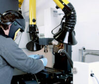 Forscher im Schutzanzug und Maske öffnet eine Batterie an einer Art Schraubstock im Labor.