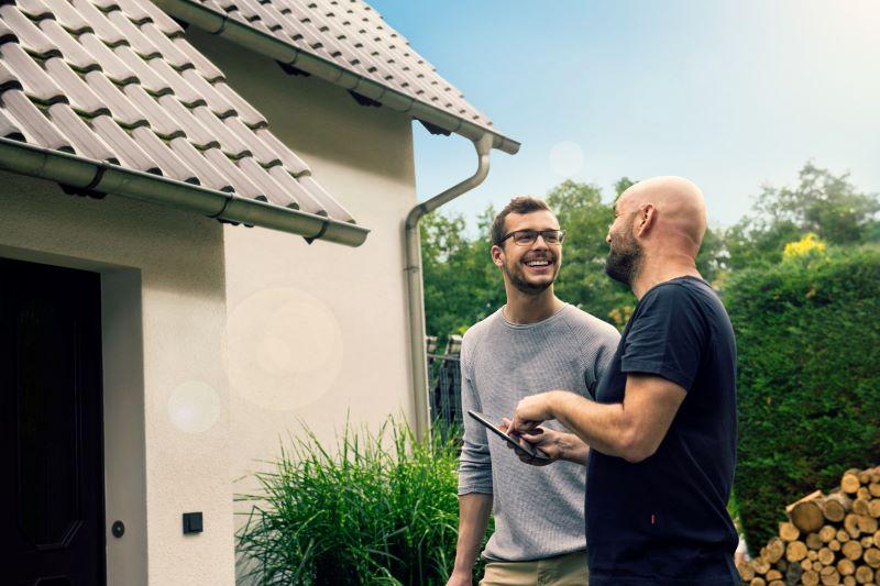 Ein freundliches Gespräch zwischen zwei Männern vor dem Eigenheim mit Taschenrechner in der Hand.