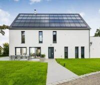 Zu sehen ist ein vorbildliches Gebäude mit einem Solarenergie-Dach, das Anforderungen einer möglichen Novelle des Gebäudeenergiegesetzes bereits heute spielend erfüllt.