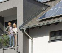 Älteres Paar betrachtet vom Balkon aus PV-Anlage auf dem Dach