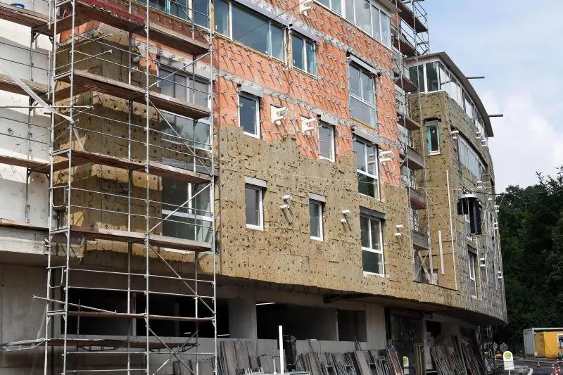 Zu sehen ist ein für die Dämmung eingerüstetes Mehrfamilienhaus. Komplettsanierungen werden in der Bundesförderung für energieeffiziente Gebäude (BEG) bessergestellt.