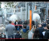 Blick durchs Publikum auf mehrere Personen, die ein rotes Band vor einer Industrie-Anlage durchschneiden: Einweihung der E-Fuel Fertigung