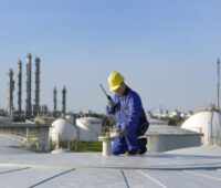 Arbeiter auf einem Tanklager und vor Hintergrund Raffinerietürme.