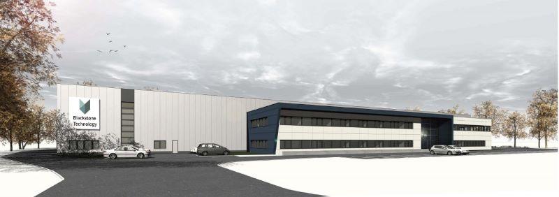 Ein modernes Fabrikgebäude vor herbstlichem Himmel.