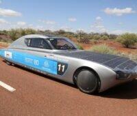 Ein Rennwagen mit Solarzellen auf einer Straße in der Wüste Australiens.