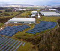 Luftbild einer Fabrik im Vordergrund mit Solaranlagen, im HIntergrund mit Windenergie.