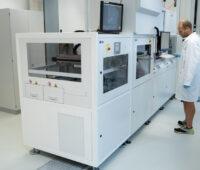 Mann in weißem Kittel steht neben weißer Maschine - Photovoltaik-Industrie 4.0