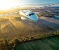 Ein Flugzeug mit DLR-Symbol fliegt über eine Landschaft zum Sonnenuntergang.