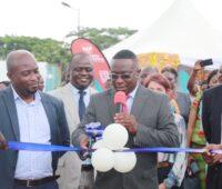 Ein Offizieller schneidet das band bei der Eröffnung der Solaranlage für die Universität in Ghana durch.