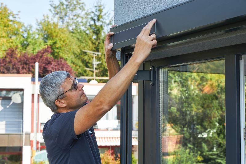 Ein Monteur bringt ein rechteckiges Solarmodul an einem Fenstersichtschutz an.