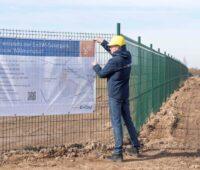 Ein Bauarbeiter mit Helm installiert ein Infoschild an einem Bauzaun. Das informiert über den geplanten Solarpark.