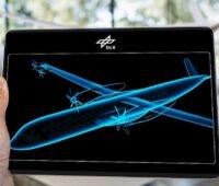 Eine Hand hält ein Tablett. Darauf die Zeichnung eines Flugzeugs