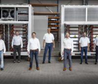 Acht Mitarbeiter vor Container mit Batterien.