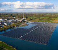 Solarmodule schwimmen auf einem See in den Niederlanden.. Links vom See befindet sich ein Industriegebiet, im Hintergrund Grünland.