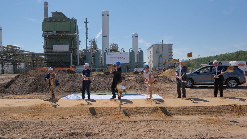 6 Personen vollziehen einen Spatenstich vor Anlagen der Chemieindustrie.