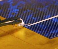 Ein Leuchtprüfgerät an blauen Solarzellen.