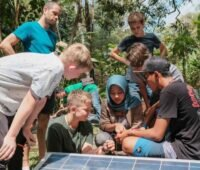 Mädchen und Jungen vor einem PV-Modul umgeben von Dschungel.
