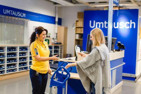 In einem IKEA-Geschäft reicht eine Kunden einer IKEA-Mitarbeiterin einen Kassenzettel, um ein Produkt abzuholen.