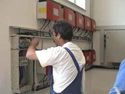Netzgekoppelte Photovoltaikanlagen: Der Handwrker installiert den Wechselrichter.