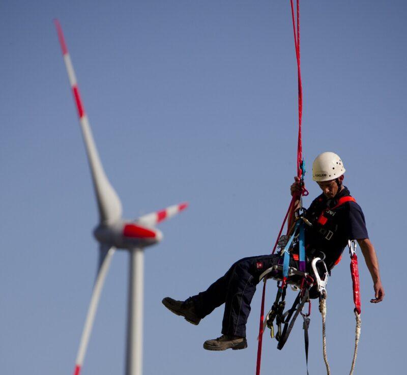 Zu sehen ist ein Arbeiter, der an einer Windenergieanlage hängt. Frauen sind in den Erneuerbaren Energien unterrepräsentiert.