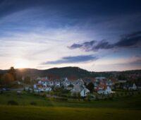 Blick auf ein Dorf am rand eines Gebirgszuges, hinter dem gerade die Sonne aufgeht.