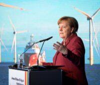 Bundeskanzlerin Merkel bei einer Rede im Hintergrund Fotos von Windkraftanlagen.