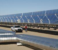 Ein solarthermisches Kraftwerk in der Wüste mit Rohren von Solarspiegeln, dazwischen ein PickUp und Arbeiter mit Helm.