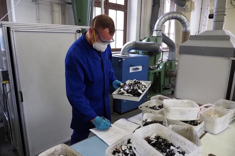 Mann mit Mundschutz sortiert geschredderte Materialien.
