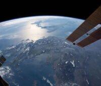 Die Erde aus dem Weltall gesehen, zwei Solarsegel am Rand.
