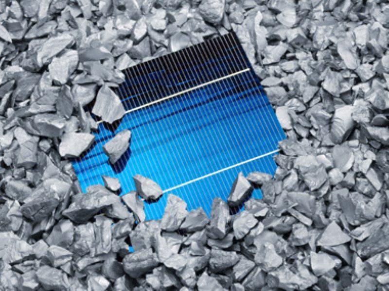 Eine bale Solarzelle liegt in kristallisierten Brocken aus Polyzilizium.