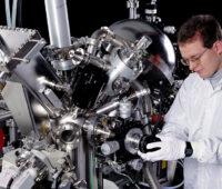 Forscher im Weißen Kittel am Elektronenspektroskop