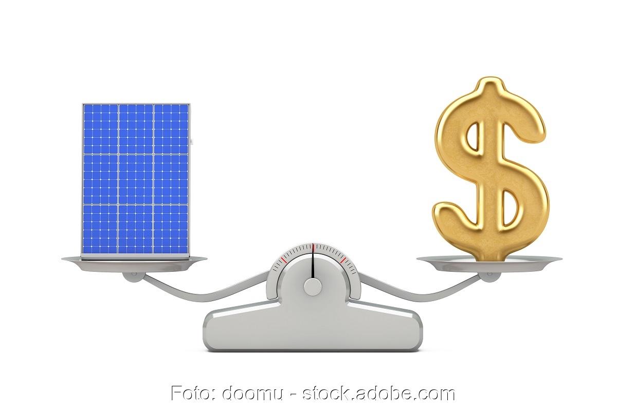 Zu sehen ist eine Waage, die PV-Module gegen Dollar aufwiegt als symbolische Darstellung der Preise für Photovoltaik-Module im November 2020.