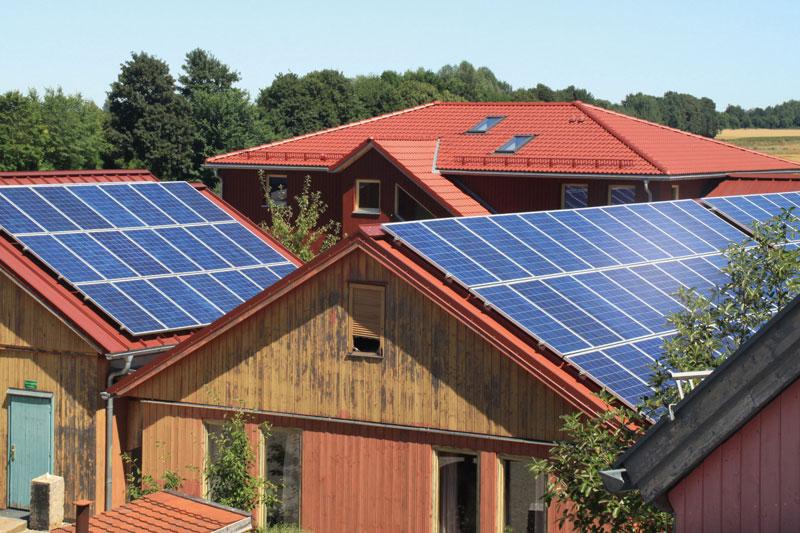 Dächer mehrerer Gebäude mit Solarstromanlagen belegt.