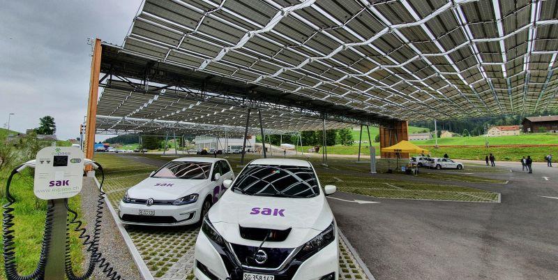 Parkende Elektroautos unter einem Solarfaltdach in der Schweiz.