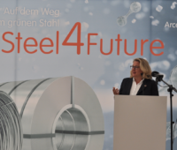 Svenja Schulze hinter Rednerpult vor einer Plakatwand von ArcelorMittal - Grüner Stahl mit Wasserstoff